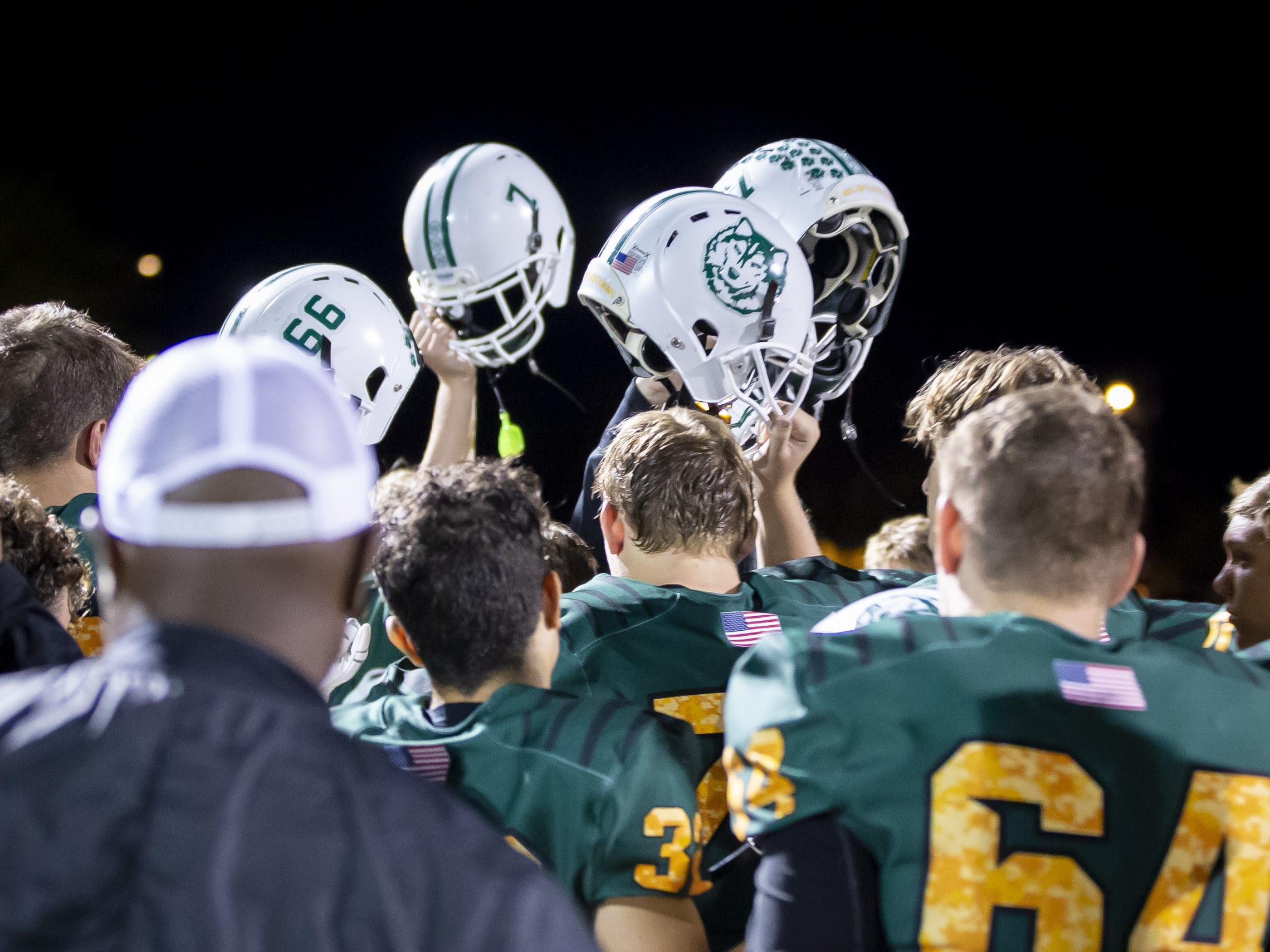 The Horizon Huskies hold up helmets following their loss against the Notre Dame Prep Saints at Horizon High School on Friday, October 5, 2018 in Scottsdale, Arizona. #azhsfb