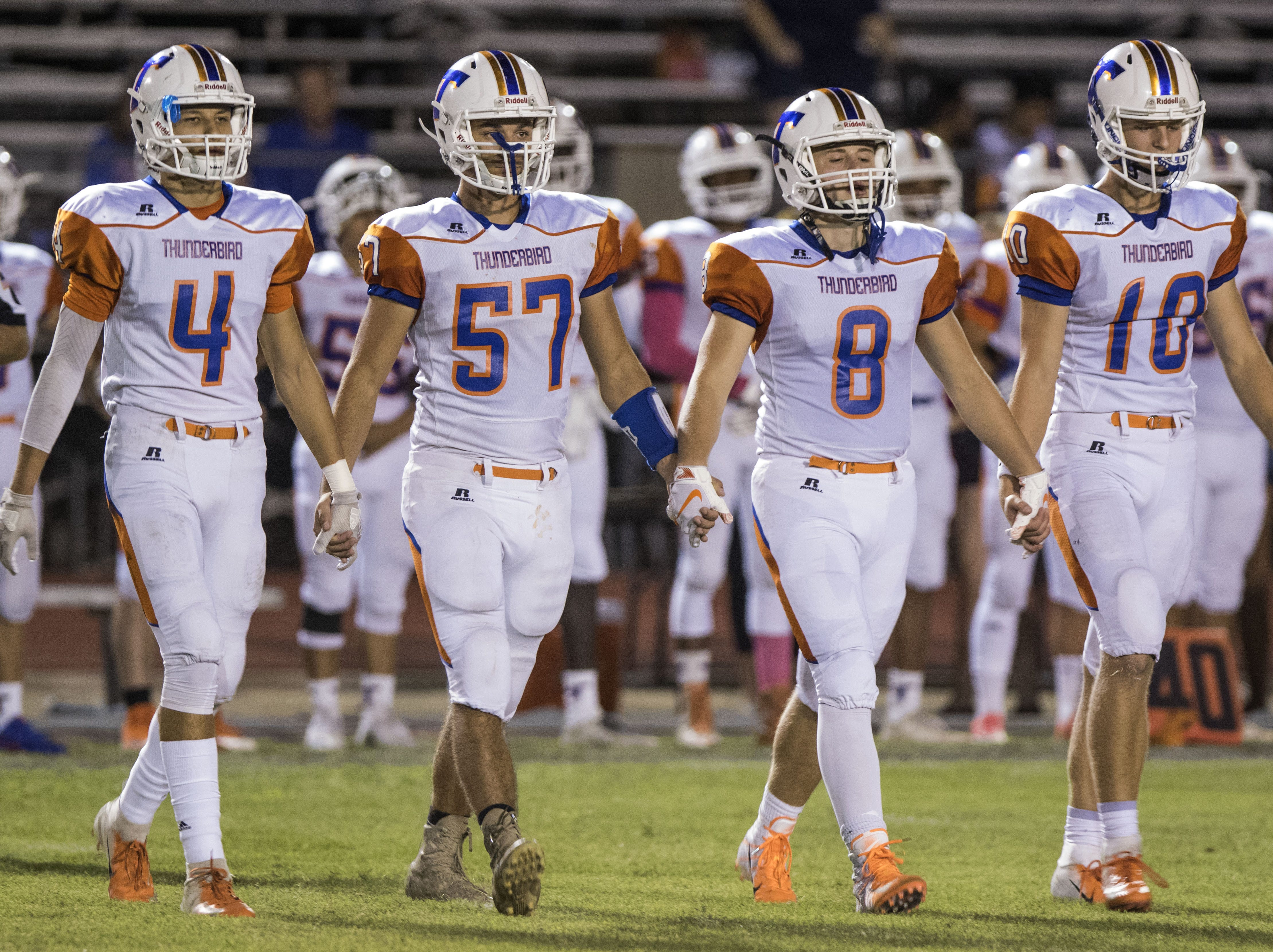 Thunderbird captians Kyle Mitchell (4), Dominick Mcnutt (57), Kain Ream (8) and Trevor Messing (10) walk to the  the coin toss before their game with Washington in Phoenix Friday, Oct. 5, 2018. #azhsfb