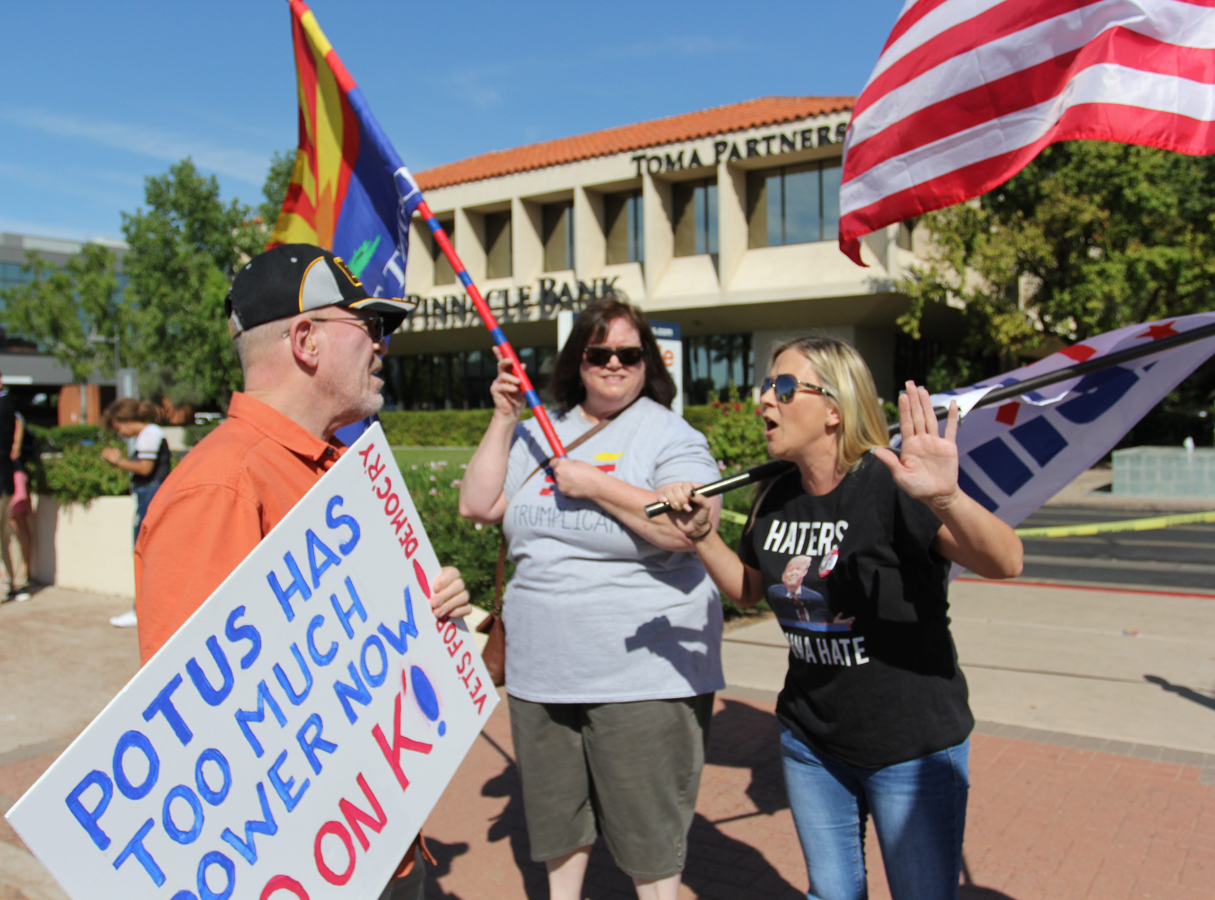 Anti-protester walk through protesters who rally outside Sen. Flake's Phoenix office on Saturday Nov. 6, 2018.
