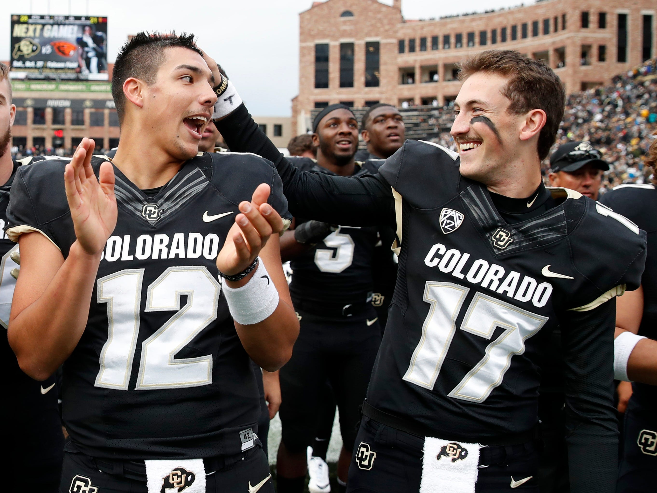 Colorado quarterback Steven Montez, left, jokes with quarterback Josh Goldin as they sing the school song after the second half of an NCAA college football game against Arizona State Saturday, Oct. 6, 2018, in Boulder, Colo. Colorado won 28-21. (AP Photo/David Zalubowski)