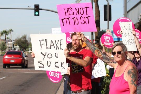 Christopher Hanlon holds sign outside Sen. Flake's Phoenix office on Saturday, Nov. 6, 2018.