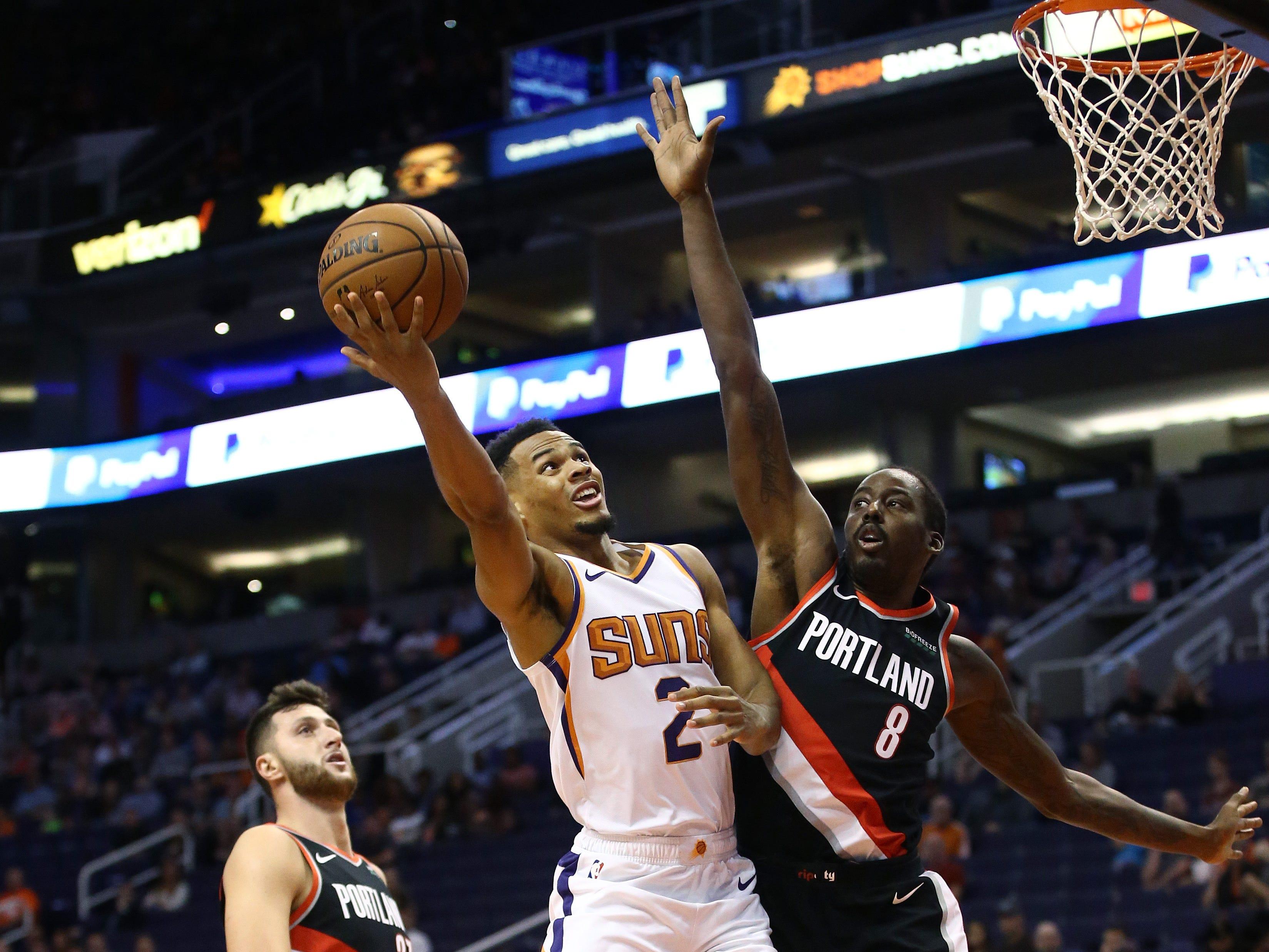 Phoenix Suns guard Elie Okobo drives to the basket against Portland Trail Blazers forward Al-Farouq Aminu during a preseason game at Talking Stick Resort Arena on Oct. 5, 2018, in Phoenix, Ariz.
