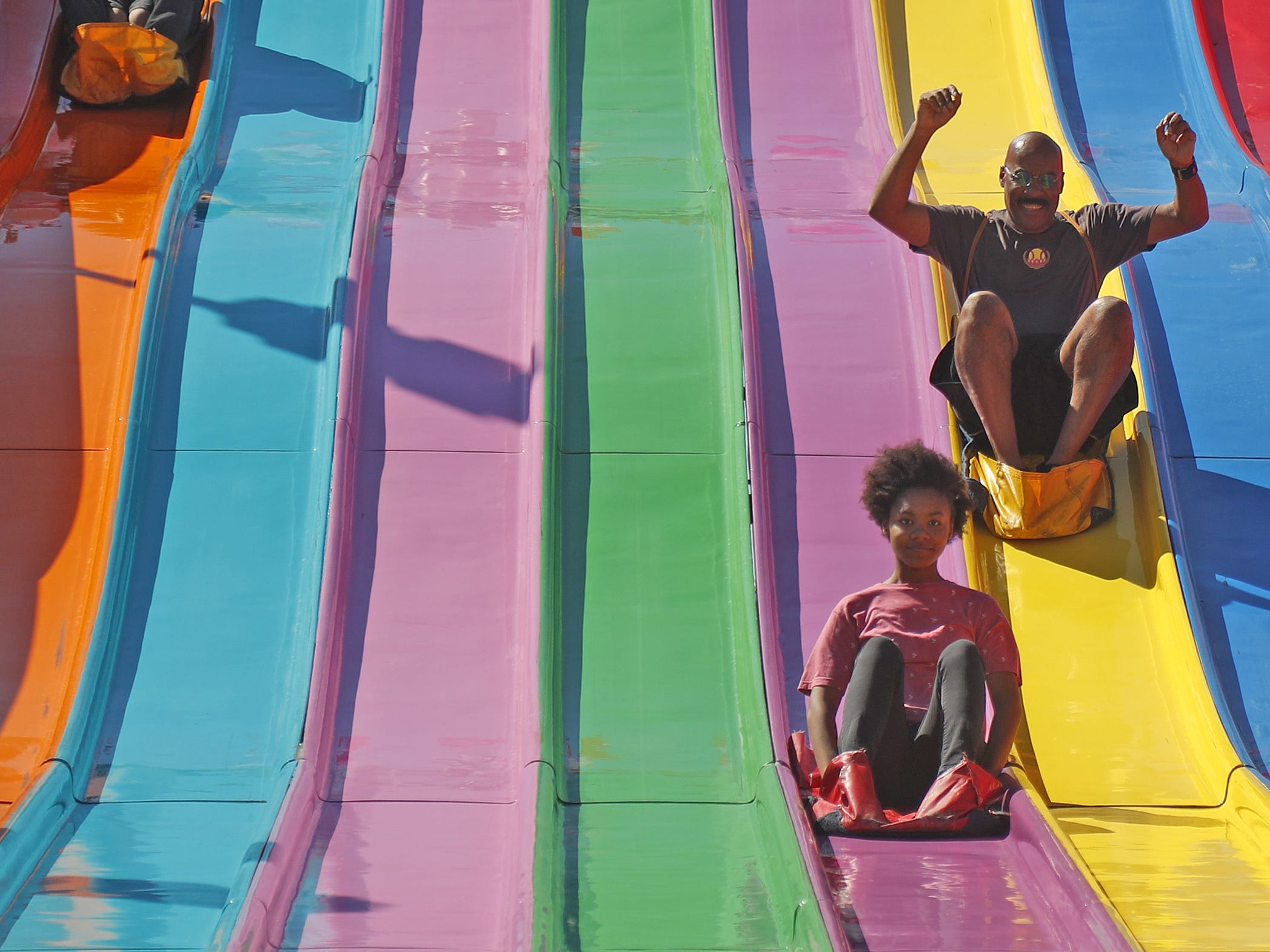 Jojo Frias (L) holds his son Jessiah Frias as Javon Frias (center pair) rides down the Euroslide with Elizabeth Frias and Ava Manager (front) beats her father Vada Manager down the slide at the Arizona State Fair in Tempe, Ariz. on October 5, 2018.