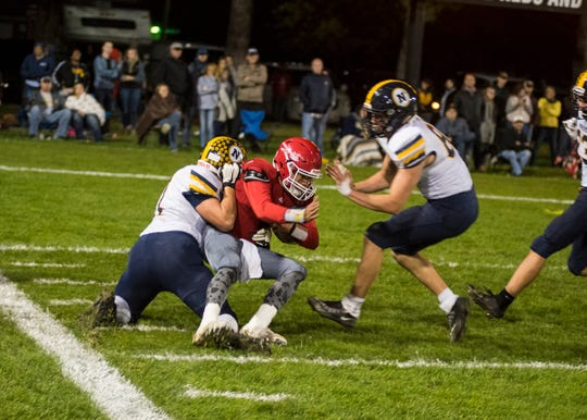 Port Huron High School quarterback Jonny Oriel (center) is brought down by Port Huron Northern High School lineman Logan Bonner just outside the end zone during the Crosstown Showdown Friday, Oct. 5, 2018 at Memorial Stadium.