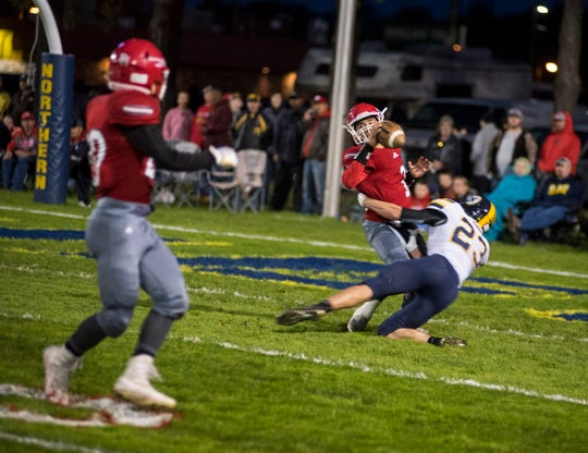 Port Huron High School quarterback Jonny Oriel is sacked by Port Huron Northern High School linebacker Austin Eagle (23) during the Crosstown Showdown Friday, Oct. 5, 2018 at Memorial Stadium.