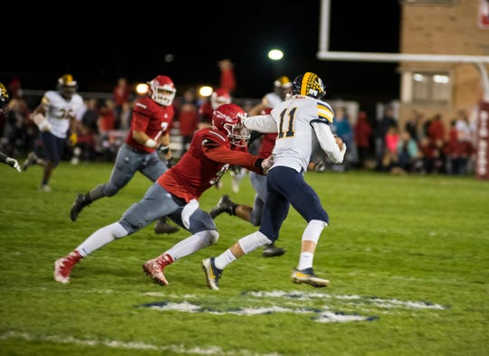 Port Huron High School linebacker Jace Mullins (9) is pushed back by Port Huron Northern High School wide receiver James DeLong as he runs the football during the Crosstown Showdown Friday, Oct. 5, 2018 at Memorial Stadium.