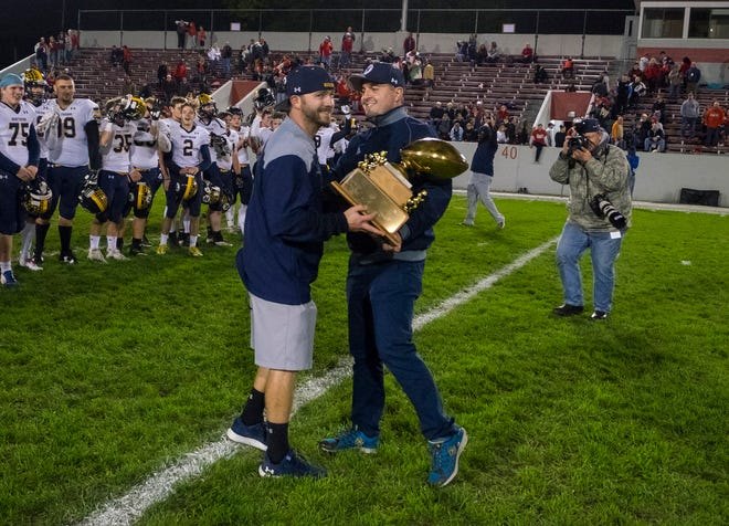 Port Huron Northern athletic director Jason Kasparian, right, hands the Brick Fowler trophy to head coach Larry Roelens after Northern defeated Port Huron High School 21-14 in the Crosstown Showdown Friday, Oct. 5, 2018 at Memorial Stadium.