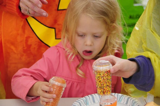 Lacey Mangas, 4,  puts sugar sprinkles on a pumpkin sugar cookie during the Pumpkin Palooza Party on Oct. 6, 2018 in Marine City