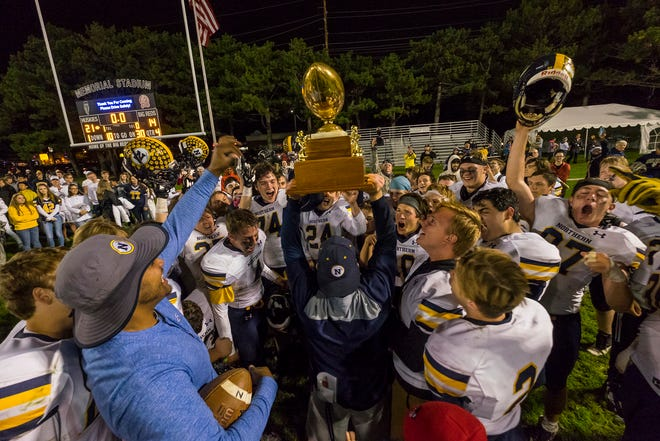 The Port Huron Northern High School football team cheers as head coach Larry Roelens, center, holds up the Brick Fowler trophy, which the team received for defeating Port Huron High School 21-14 in the Crosstown Showdown Friday, Oct. 5, 2018 at Memorial Stadium.