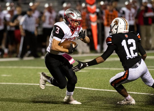 Dover's Derek Arevalo (3) looks for running room against York Suburban's David Moye (12) during a Division II football game at York Suburban High School, Friday, Oct. 5, 2018. The Dover Eagles beat the York Suburban Trojans, 34-12.
