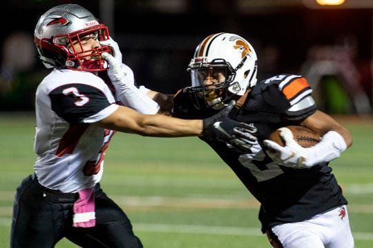 York Suburban's Savion Harrison (2) stiff arms Dover's Derek Arevalo (3) during a Division II football game at York Suburban High School, Friday, Oct. 5, 2018. The Dover Eagles beat the York Suburban Trojans, 34-12.