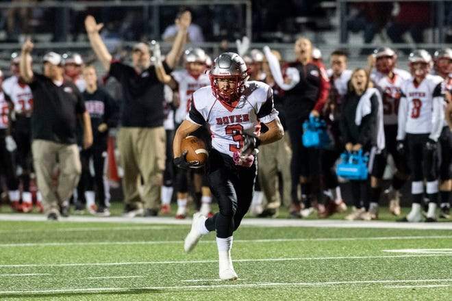 Dover's Derek Arevalo (3) runs the ball en route of a touchdown as the Eagles' sideline cheers during a Division II football game at York Suburban High School, Friday, Oct. 5, 2018. The Dover Eagles beat the York Suburban Trojans, 34-12.