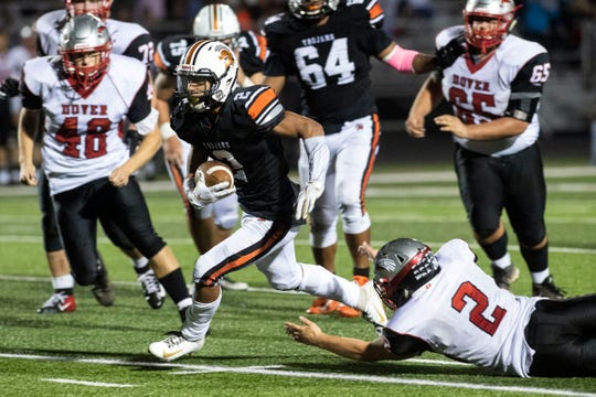 York Suburban's Savion Harrison (2) runs the ball down the field as Dover's Brandon Lawyer (2) extends out during a Division II football game at York Suburban High School, Friday, Oct. 5, 2018. The Dover Eagles beat the York Suburban Trojans, 34-12.