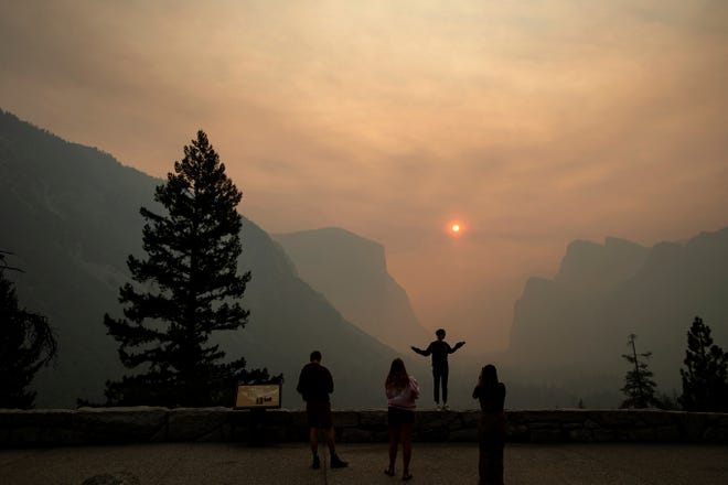 In this July 25, 2018 file photo, Hannah Whyatt poses for a friend's photo as smoke from the Ferguson fire fills Yosemite Valley in Yosemite National Park, Calif. Authorities say the Ferguson fire, that killed two firefighters and destroyed nearly a dozen buildings in Northern California, was caused by a vehicle. The U.S. Forest Service on Friday, Oct. 5, 2018, said investigators determined that a hot catalytic converter ignited dry roadside vegetation. However, investigators haven't identified the vehicle.
