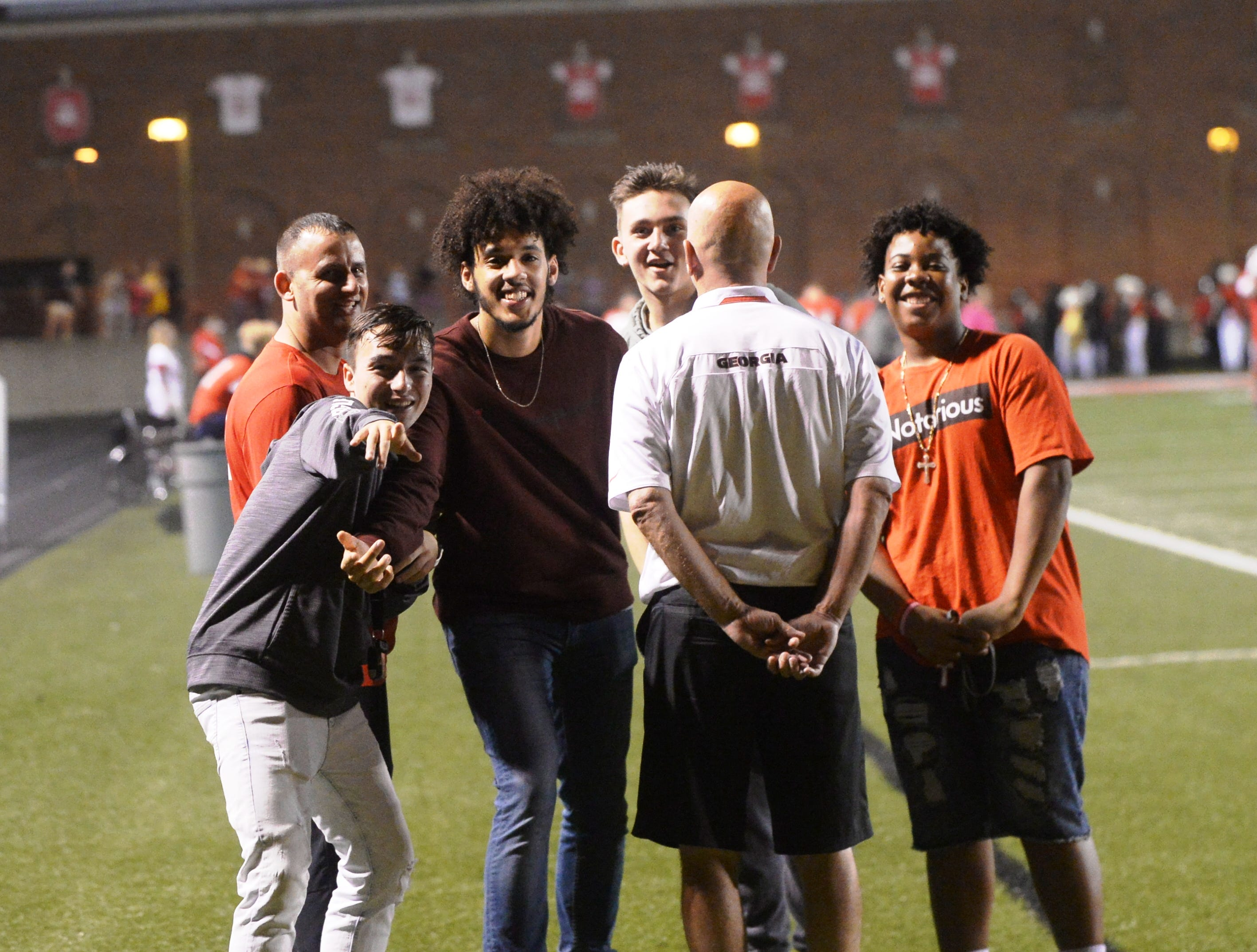 Members of the Richmond High School basketball team smile on the sidelines during a 27-26 football loss to Anderson Friday, Oct. 5, 2018 at Lyboult Field.