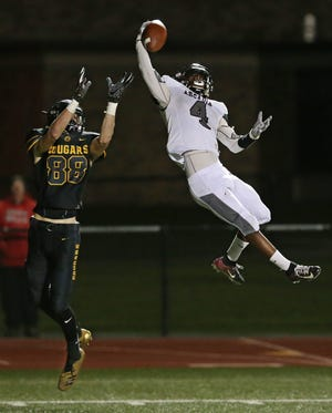Arcadia's K'myn Crumity, right, goes way up to block a pass attempt to HF-L's Derek Childs in the first half.