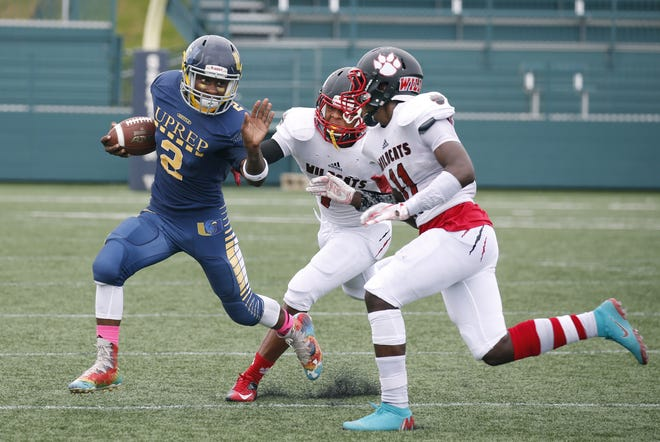UPrep's Perryione Brown runs the ball away from Wilson's Desi Floyd Jr. and Jervon Johnson in the second quarter at Marina Auto Stadium.
