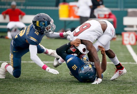 UPrep's No.10 Na'Zea Fowlks takes down Wilson's Khajana Smith with help from Jarvis Alexander in the first quarter at Marina Auto Stadium.