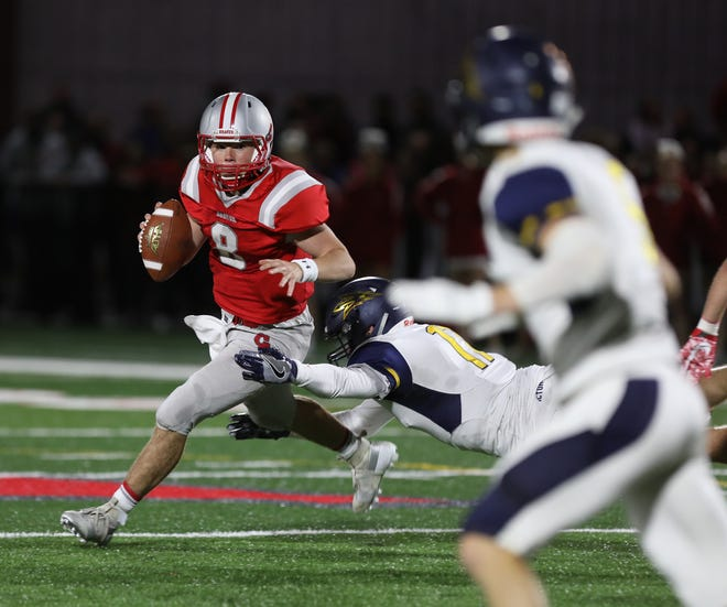 Canandaigua quarterback Jack Johnston looks for an open receiver while avoiding Victor's A.J. Tillotson during the Braves' 12-0 win on Friday night.