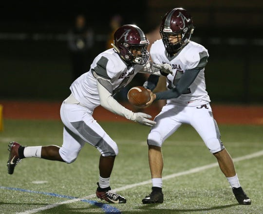 Arcadia quarterback Brian Shonitsky, right, hands the ball off to running back K'myn Crumity.