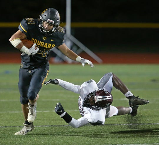 Honeoye Falls-Lima's Mason Ferrara, left, shakes off the diving tackle attempt by Greece Arcadia's JaQuan Davis on his way to a big gain in the first half during their game at Honeoye Falls-Lima High School Friday, Oct. 5.