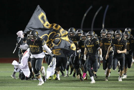 HF-L's Josh Kosciol, left, carries the team flag as he leads his team onto the field to take on Arcadia.