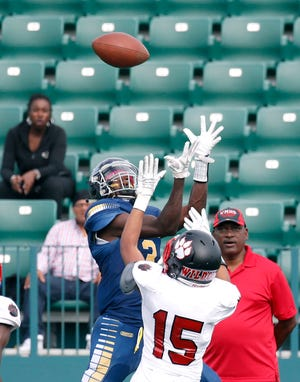 UPrep's Jamir Miller catches a pass next to Wilson's Tory Bradley in the second quarter at Marina Auto Stadium.