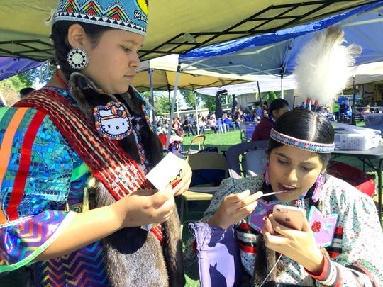 Hummingbird Montgomery, left, watches as head teen girl Ariana Murillo applies makeup Saturday at the Stillwater Powwow. They came from Fresno to compete at the Anderson fairgrounds.
