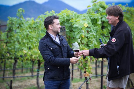 Jim Bernau (right) hands a glass of Willamette Valley Vineyard merlot, made with Rogue Valley fruit, to Justin King (left) of King Estate Winery in Eugene. The two wineries will partner with Sylvan Ridge Winery to make a limited release called Solidarity Vintage.