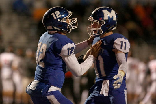 Erik Barker (12) and Noah Bach (11) celebrate after Barker makes a touchdown in the second half of the Sprague vs. McNary football game at McNary High School on Friday, Oct. 5.