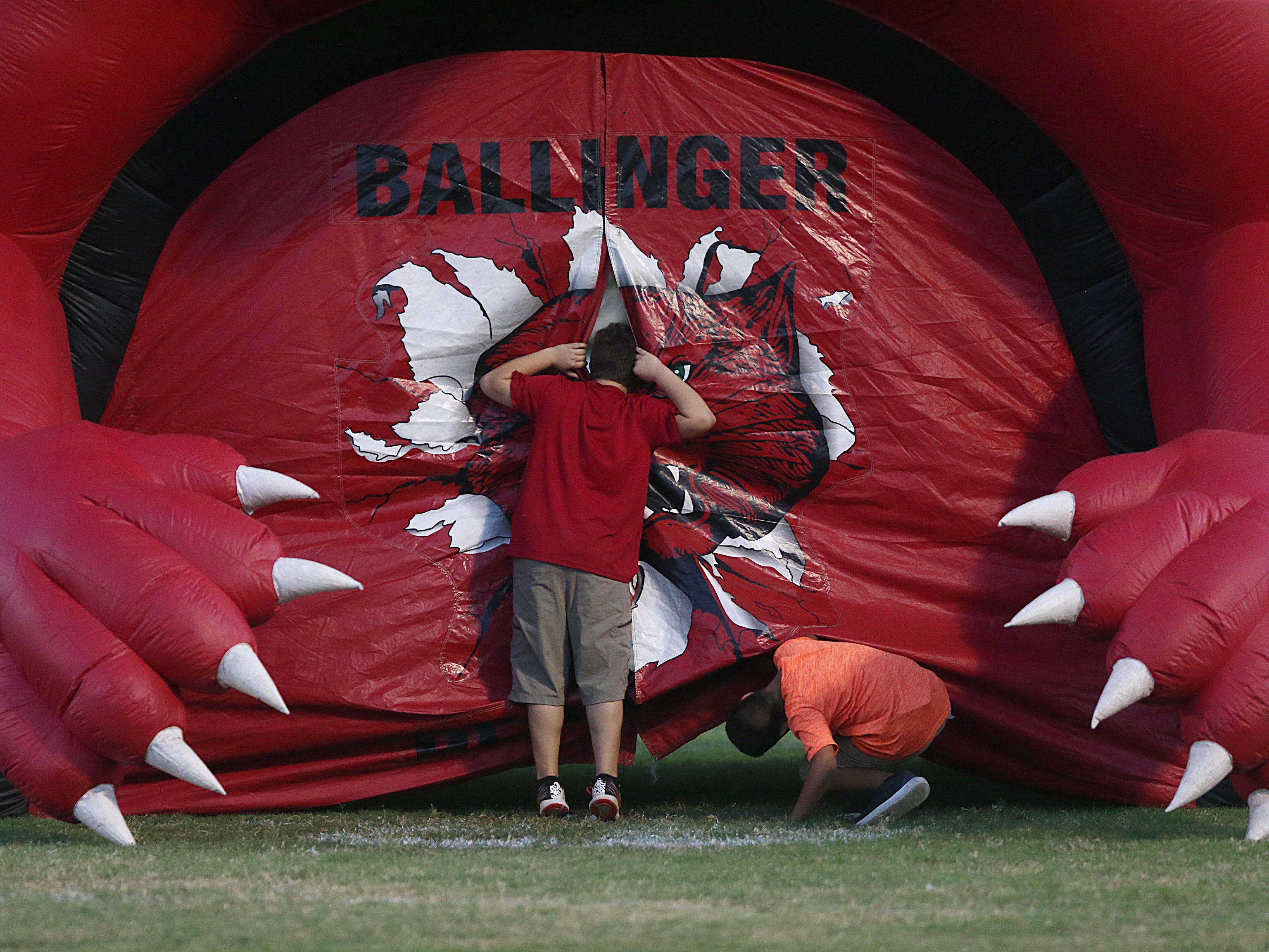 Kids take a sneak peek inside the Ballinger's inflatable before the game Friday, Oct. 5, 2018, between Ballinger and Anson.