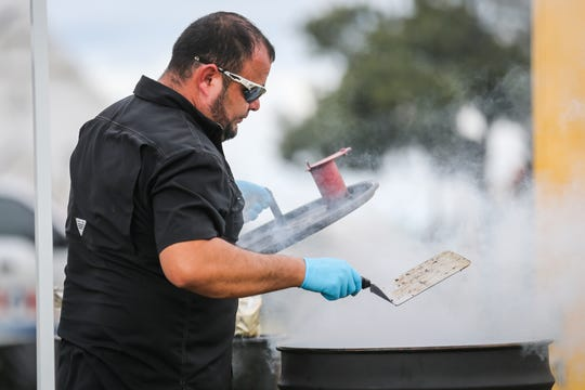 Johnny Montalbo from Del Rio pulls meat from a smoker during Brews, Ewes & BBQ Saturday, Oct. 6, 2018, at El Paseo de Santa Angelo.