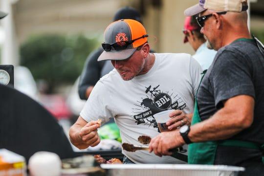 Glyn Sudduth and Jay O'Harrow sample meats during Brews, Ewes & BBQ Saturday, Oct. 6, 2018, at El Paseo de Santa Angelo.
