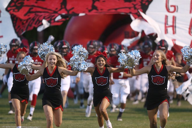 Ballinger's cheerleaders and football players rush out of the inflatable before the game Friday, Oct. 5, 2018, between Ballinger and Anson.