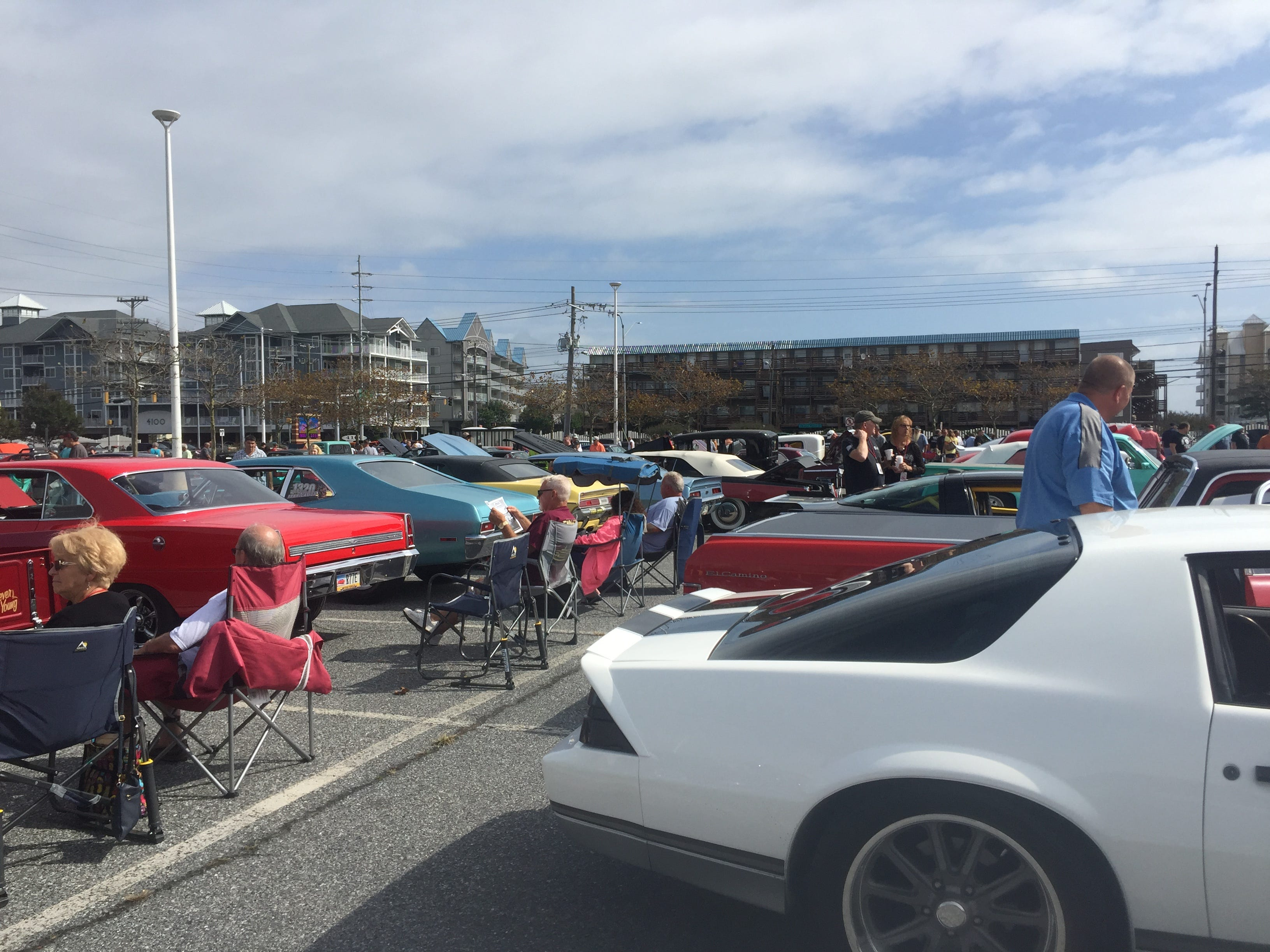 Many car enthusiasts sit in chairs beside their vintage vehicles, striking up conversations with other Endless Summer Cruisin' event attendees.
