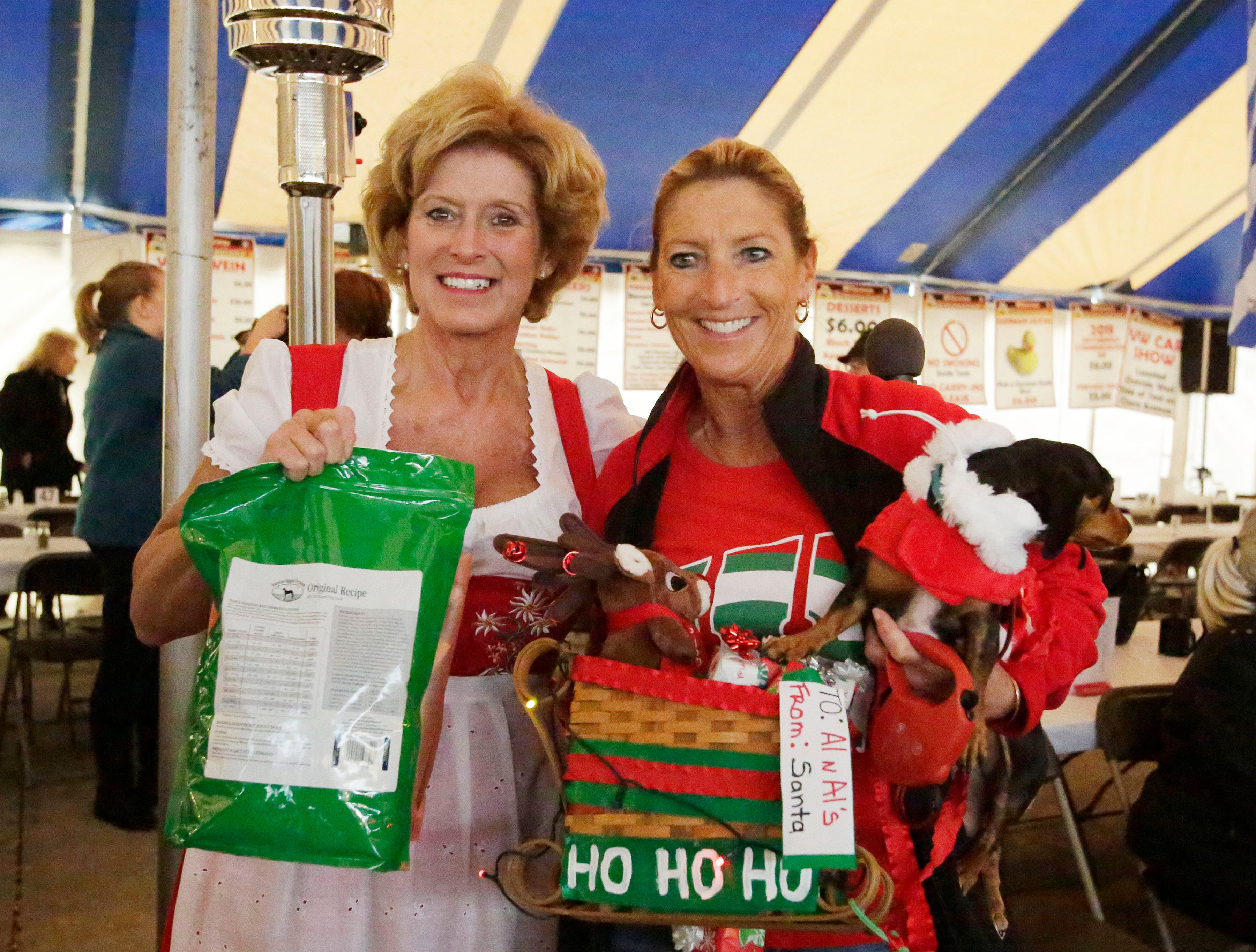 Al and Al's Susie Patterson, left, poses with Janine Blomberg of Sheboygan with her dog Olivia who was decorated as a holiday sled which won in the dog costume contest at Oktoberfest, Saturday October 6, 2018, in Sheboygan, Wis.