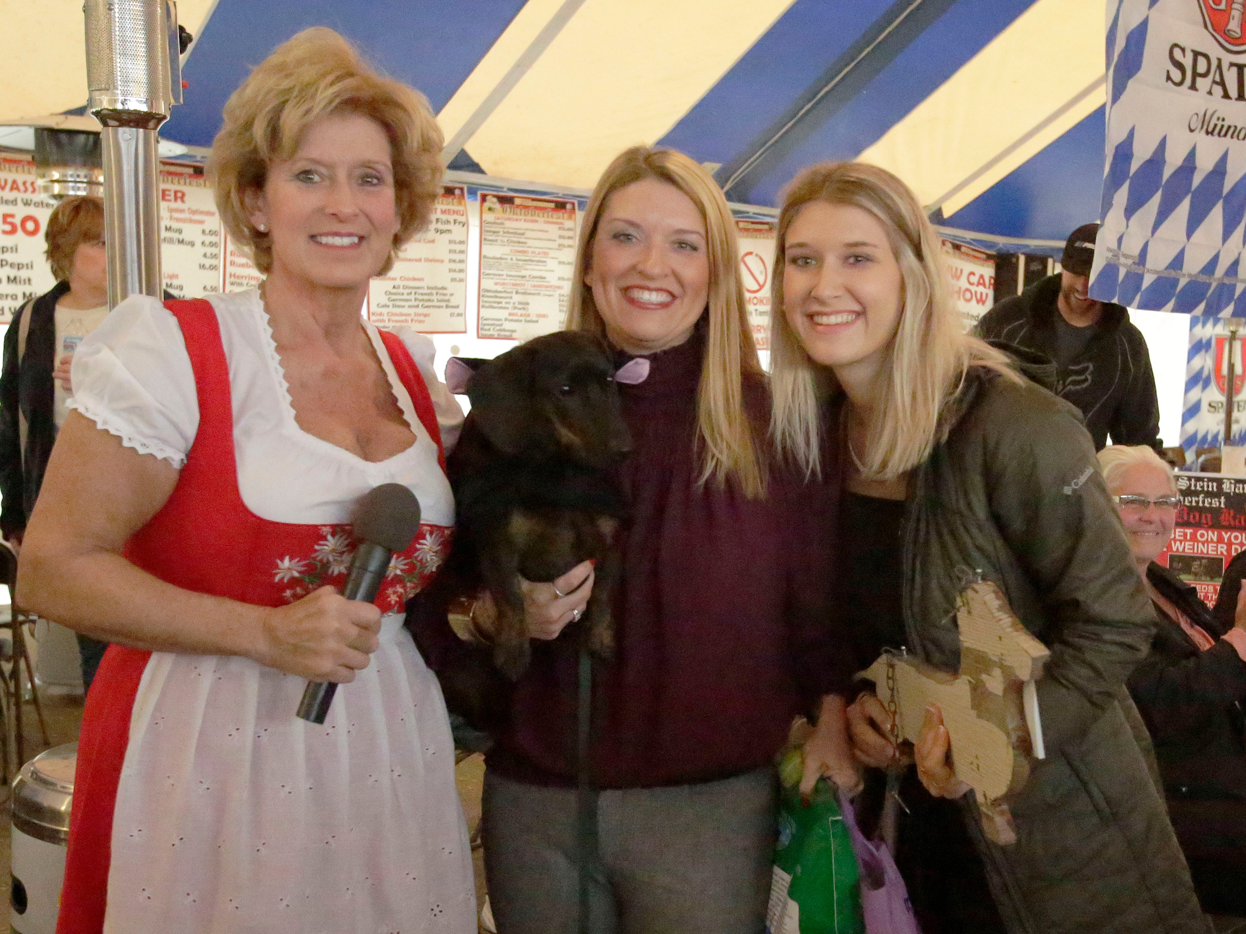 Al and Al's Susie Patterson, left, poses with Weiner Dog race winners Laura and Sydnee Pribbernow of Sheboygan, Saturday October 6, 2018, in Sheboygan, Wis. According to Laura Pribbernow her secret was a piece of sausage she had waiting for the dog at the finish line.