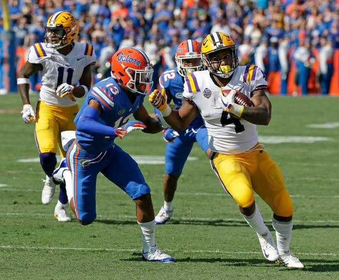 LSU running back Nick Brossette, right, runs for a gain before he is tackled by Florida safety Donovan Stiner (13) during the first half of an NCAA college football game, Saturday.
