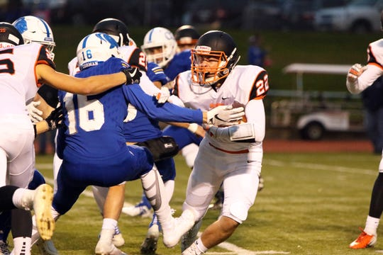 Hayden Hegg of Huron is grabbed and tackled by Logan Jones of O'Gorman during Friday night's game in Sioux Falls.