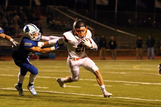 Landon Hegg of Huron is pulled down from behind by Beau Blount of O'Gorman during Friday night's game in Sioux Falls.