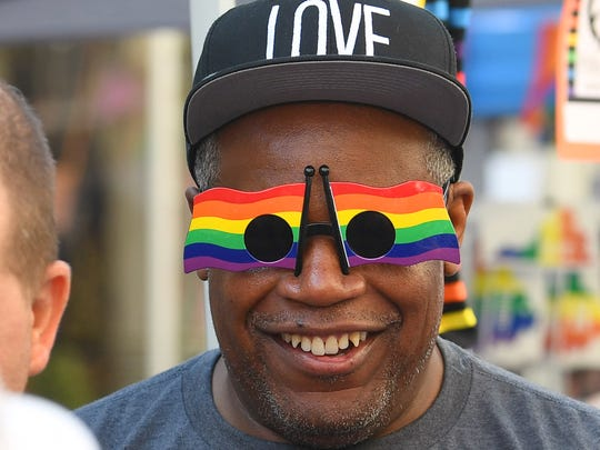 """Dennis Smith of Fishersville smiles as he wears a """"love"""" hat and rainbow flag glasses while hanging out with co-workers from Hershey's in Stuarts Draft. They attend the Staunton Pride festival together in downtown Staunton on Saturday, Oct. 6, 2018."""
