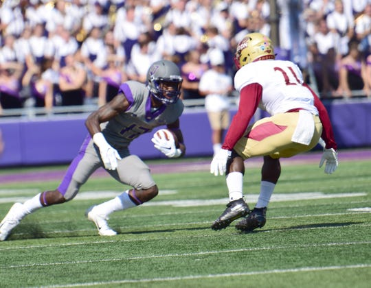 James Madison's Kyndel Dean tries to avoid Elon's Greg Liggs after making a first-half reception during the Dukes' 27-24 Colonial Athletic Association loss on Saturday, Oct. 6, 2018, at Bridgeforth Stadium in Harrisonburg, Va.