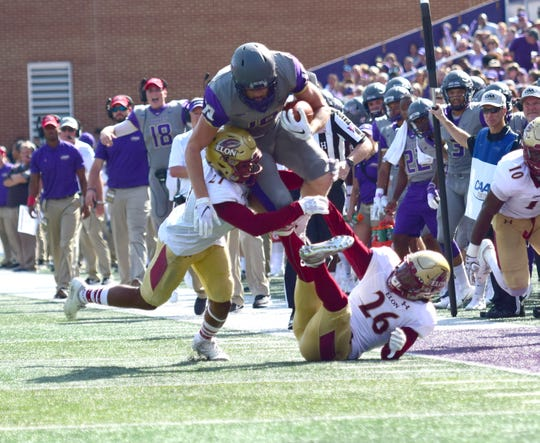 James Madison's Riley Stapleton vaults an Elon defender for a first down inside the red zone during the Dukes' 27-24 Colonial Athletic Association loss to the Phoenix on Saturday, Oct. 6, 2018, at Bridgeforth Stadium in Harrisonburg, Va.