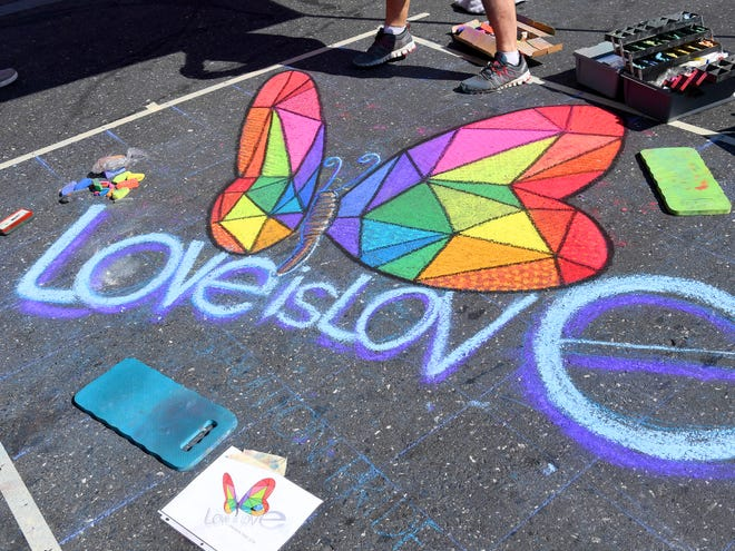 """An chalk art creation by artist Robert Mott of Harrisonburg features a butterfly with the words """"love is love"""" on East Beverley Street at the Staunton Pride festival in downtown Staunton on Saturday, Oct. 6, 2018."""