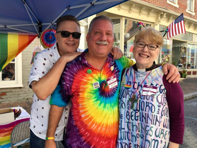 Married at First Presbyterian Church in Staunton, Gary Wilson and Brad Furr stand with their pastor, Rev. Karen Allamon, at Staunton Pride on Beverley Street, Saturday, Oct. 6, 2018.