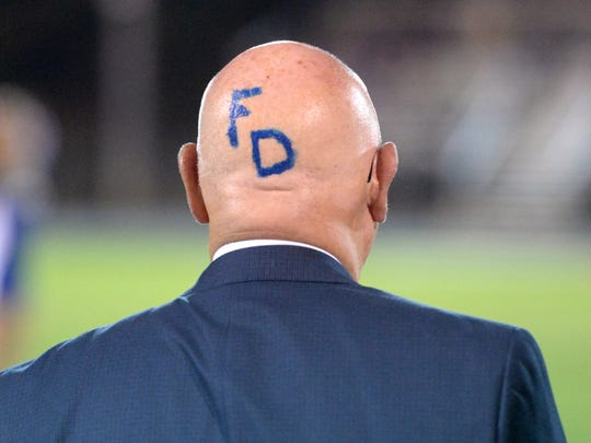 Fort Defiance principal Larry Landes shows his school pride during Friday night's football game.