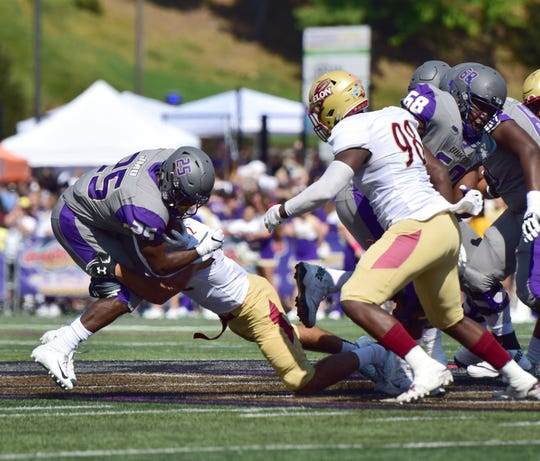 James Madison's Cardon Johnson is brought down by Elon's Zack Monson after a short gain during the first half of the Dukes' 27-24 Colonial Athletic Association loss Saturday, Oct. 6, 2018, at Bridgeforth Stadium in Harrisonburg, Va.