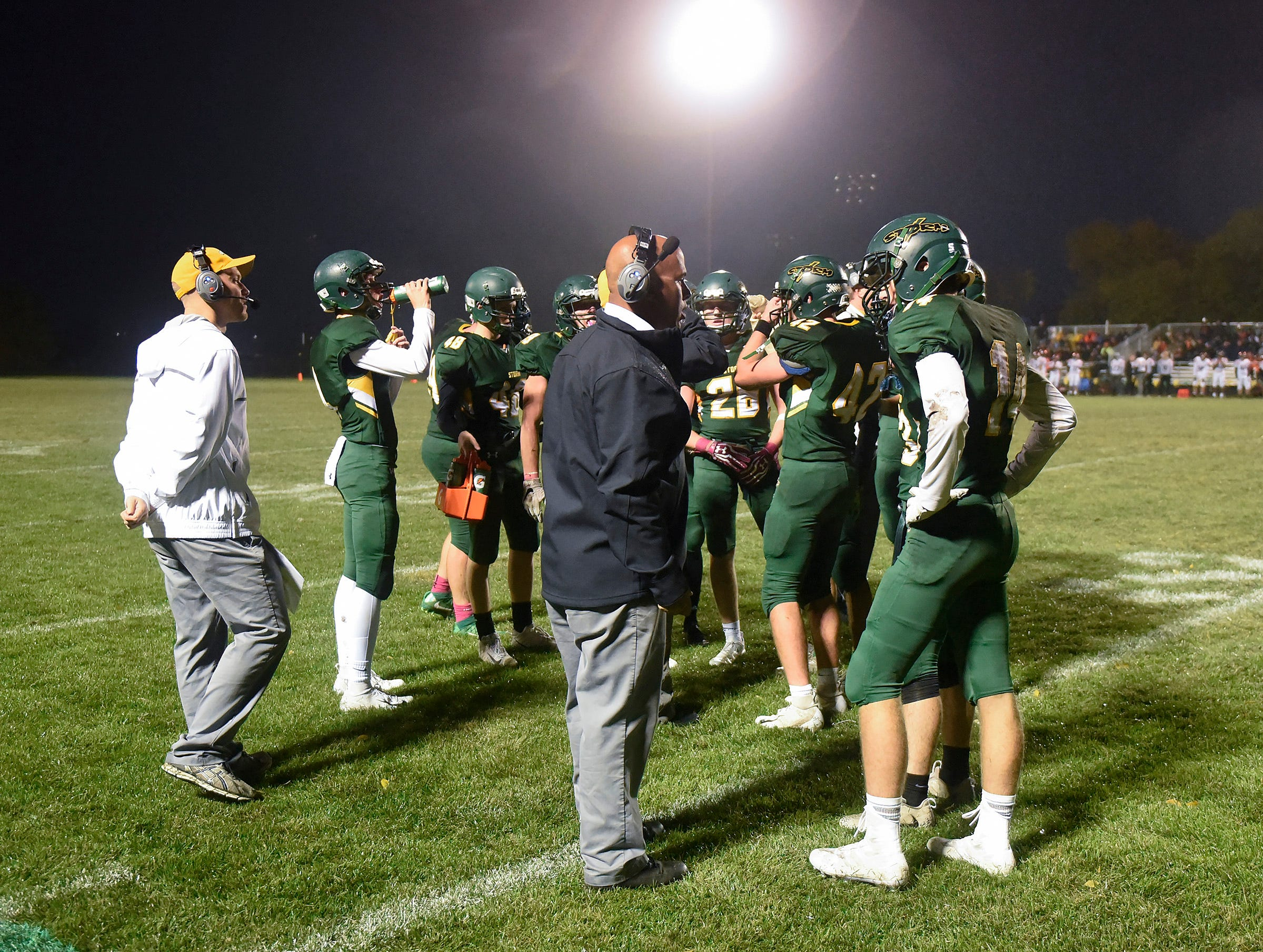 Sauk Rapids players and coaches talk during a timeout during the first half Friday, Oct. 5, in Sauk Rapids.