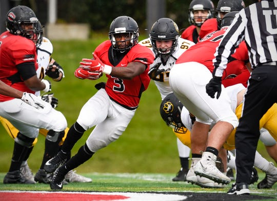 St. Cloud State's running back Gregory Lewis breaks through the line against Wayne State in the first half Saturday, Oct. 6, at Husky Stadium.