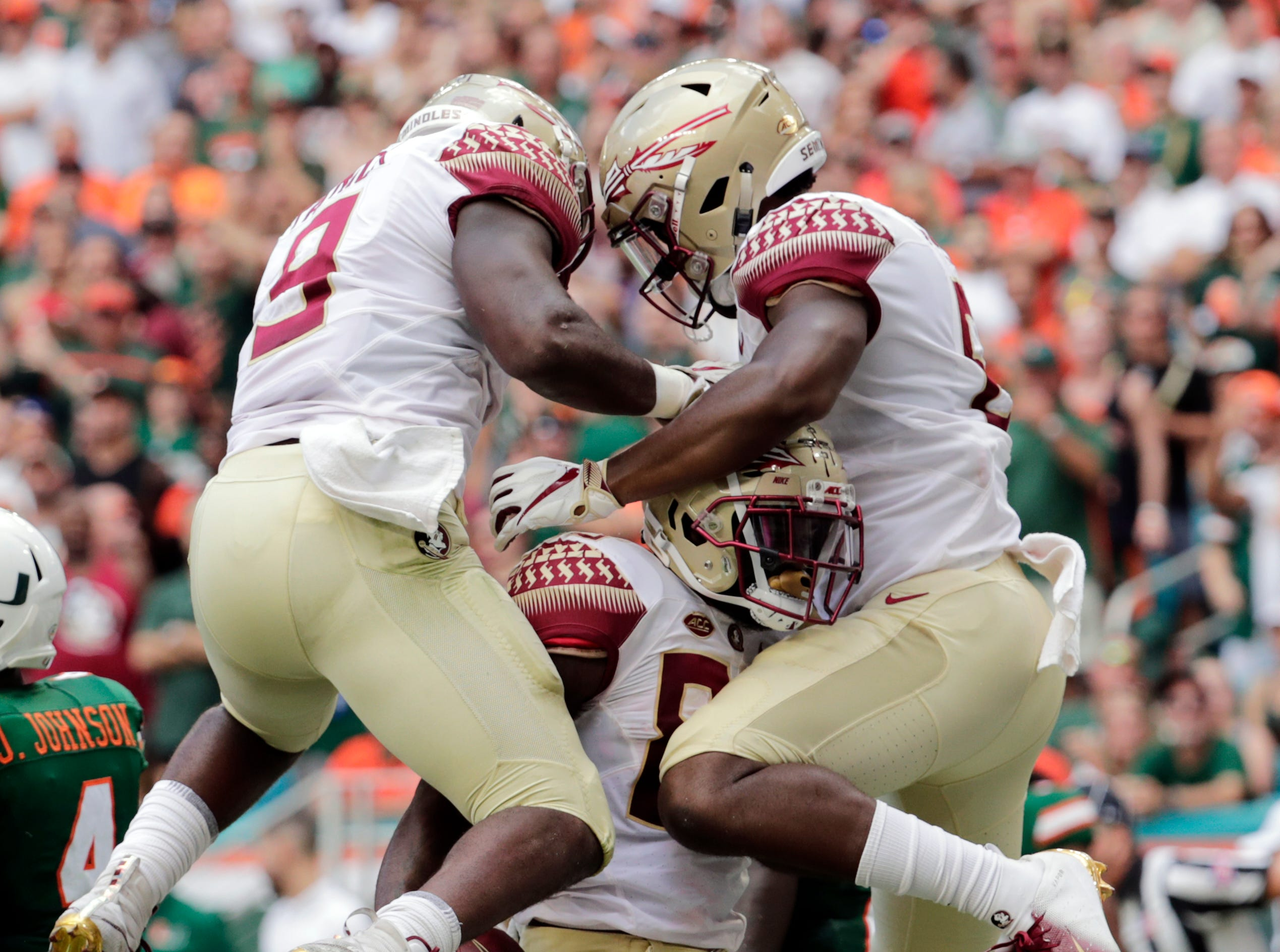 Florida State wide receiver Keith Gavin, center, celebrates with running back Jacques Patrick (9) and tight end Tre' McKitty, right, after scoring a touchdown during the first half of an NCAA college football game against Miami, Saturday, Oct. 6, 2018, in Miami Gardens, Fla. (AP Photo/Lynne Sladky)